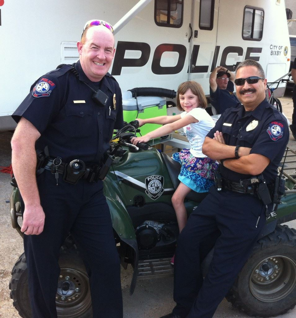 Reserve Unit Officers Standing Next to Young Girl on ATV
